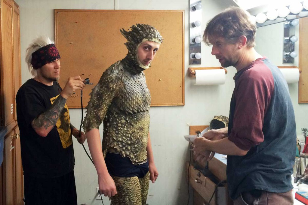 """Актёра Райана Бейла гримируют и одевают для роли полностью преобразившегося Человека-ящерицы в """"Секретных материалах""""."""